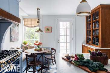A new built-in banquette with durable tweed seat cushions hugs the corner of the kitchen, creating a cozy breakfast nook that overlooks the back garden.