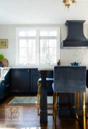 Bold navy blue cabinetry is balanced with large windows allowing light to stream into the kitchen.