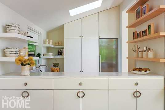 Pottery by Dana Brandwein of DBO Home populates the kitchen's open shelves.