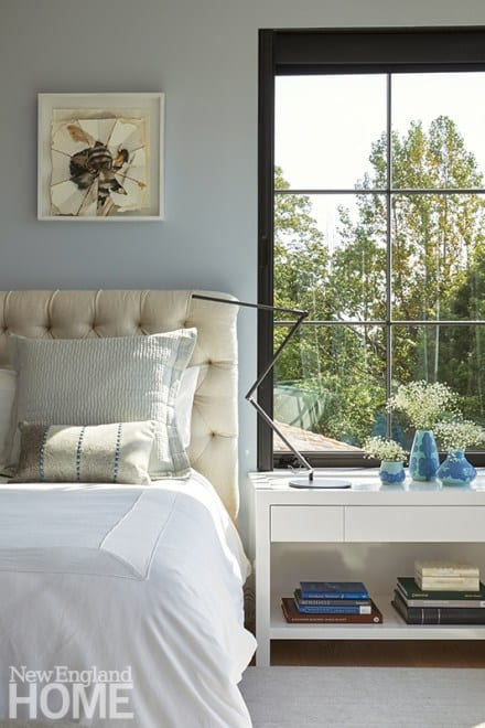 Windows wrap around the corner of the light-filled main suite, allowing sight lines to move across multiple walls; artwork by Randy Orzano, Vincent's cousin, hangs above the bed.