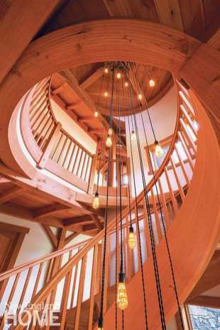 A cascading light fixture adds a dose of drama to the helical staircase, which is housed in the stone silo.