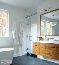 The main bath features a pendant light by Robert Abbey as well as walnut floating cabinetry built by Whitaker Hartt Cabinetry