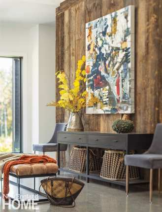 A wall comprised of wide-plank flooring reclaimed from a Vermont barn is a backdrop to a Seb Sweatman painting and is fronted by a Room & Board console table and a leather bench from Restoration Hardware.