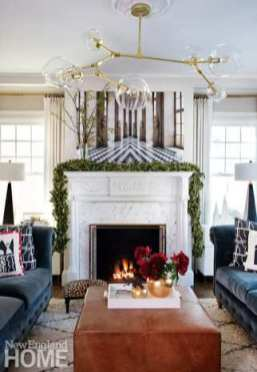 : A simple bay-leaf garland complements Sarah Winchester's own fine art print of Versailles above the mantel in the living room, while a red peony bouquet provides pop on the coffee table.