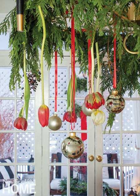 In the dining room, Winchester suspends tulips, greens, and ornaments from a chandelier.