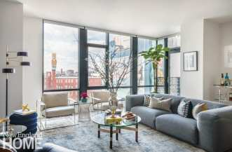 Masculine condo in Boston with a gray sofa and large windows