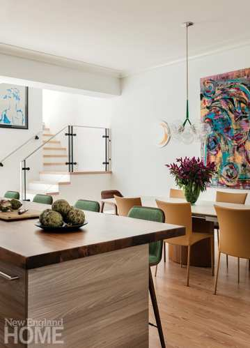 A light fixture by PELLE hangs above a table and chairs from Casa Design Group in the dining area; the artwork is by Adrienne Schlow.
