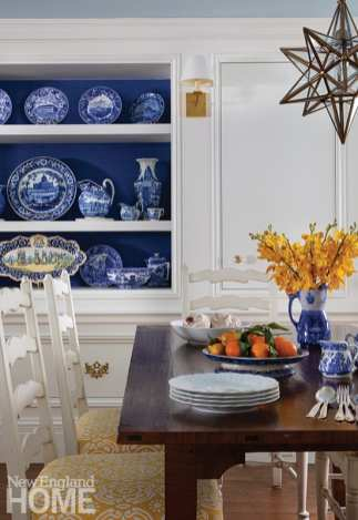 The owners' collection of Staffordshire dinnerware, displayed in the dining area, inspired designer Gerald Pomeroy's choice of the garden level's blue-and-white palette.