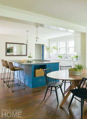 The kitchen island is topped with leathered Nero Mist granite and painted Farrow & Ball Hague Blue. To seamlessly tie together the home, all the walls in the public spaces got a coat of Benjamin Moore Light Pewter paint.