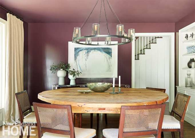 Dining room with round table and mauve walls.