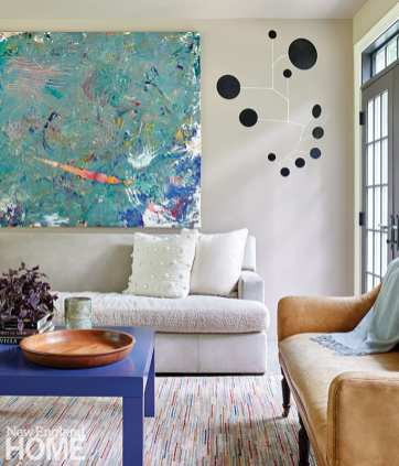 Sunroom with black mobile and colorful artwork.
