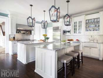 A dark and dated cherry kitchen with green marble countertops was refreshed with quartzite surfaces and pendants from The Urban Electric Co.