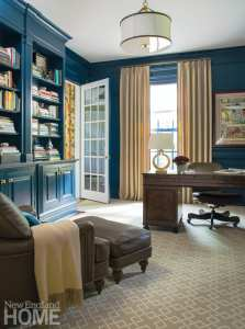 """Walsh updated the library by painting the existing cherry cabinetry a custom high-gloss blue: """"The cherry cabinetry made it feel much too masculine,"""" she explains."""