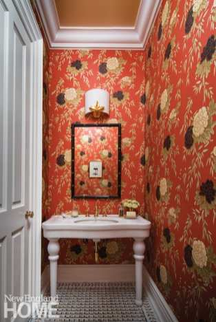 A Harlequin wallpaper envelops the powder room, which contains a mirror from J. Pocker, a sconce from Objet Insolite, and Waterworks floor tile.