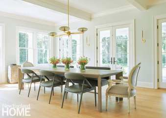 Modern and traditional meet in the dining room, where contemporary Jayson Home side chairs in wood and gray leather are paired with the homeowners' own antique head chairs.