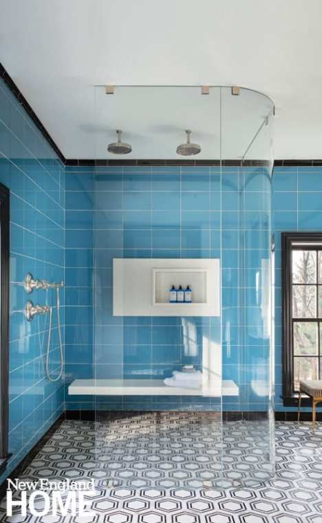 Shower with glass door and bright blue tile