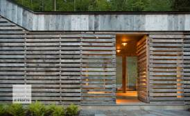 When closed, this door becomes almost invisible next to the slatted windows and siding. Incorporating weatherproof gaskets and seals, concealed hinges and low profile handles and locking hardware was a technical challenge, but keeping the uninterrupted façade was paramount to the overall aesthetic. Photo by Jim Westphalen.