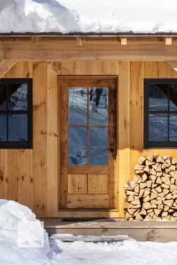 Made from reclaimed materials for a Net Zero home, this door needed a rustic look, but also needed to be able to withstand the extreme weather cycles of a Vermont mountainside, providing flawless operation and insulation year-round. Photo by Lindsay Selin.