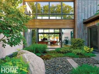"""A view from the magnificent courtyard looks into the same living area with sliding glass walls on either end. """"The connection to the garden is very immediate,"""" says Jana Bryan, senior landscape architect at JMMDS and project lead."""