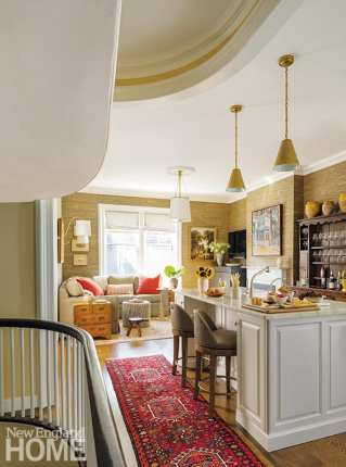 Payne | Bouchier Fine Builders opened up the kitchen to the stairway and designed a center island that involved some tricky plumbing. Nearby, Rivoli reimagined the formal dining area as a cozy family room cocooned in Phillip Jeffries grasscloth, while the wall adjacent to the fireplace provided the perfect spot for an antique Welsh teacup cupboard.
