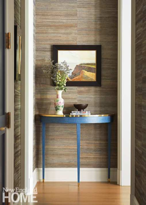 Hallway with grasscloth walls and blue demi-lune table