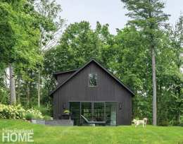 An unassuming style and black stain help this barn fit in with its New Canaan neighbors, while aluminum-framed glass doors and square-edged eaves add a touch of modernity.