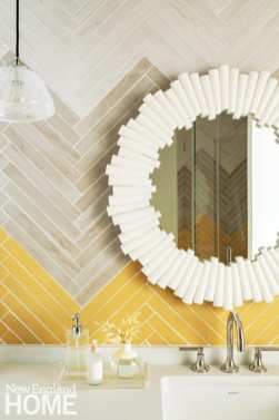 Bathroom with yellow and gray chevron tile and white mirror.