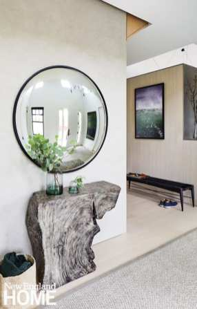 A convex mirror by RH and a Phillips Collection console greet guests in the entry