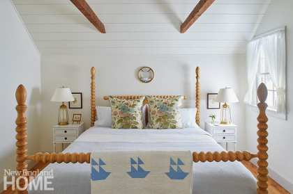 Maine cottage bedroom with white walls and rustic beams