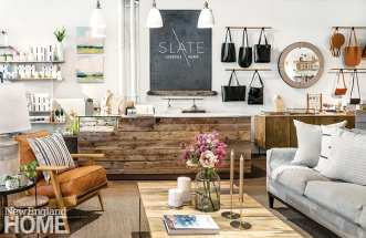 The paintings to the left of the Slate logo are by local artist Julia Purinton, while the adjacent shelves house Lafco candles and diffusers.