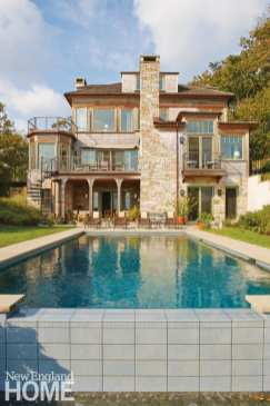 Three story shingle style home with a pool.