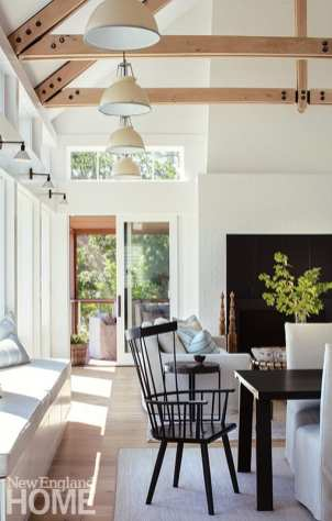 """Hardware details on the trusses above cued the choice of the black Windsor chairs and dining table that share the main living space. """"The details really had this incredible connection to the natural surroundings that made it easy to pull together our design concept,"""" says designer Liz Stiving-Nichols."""