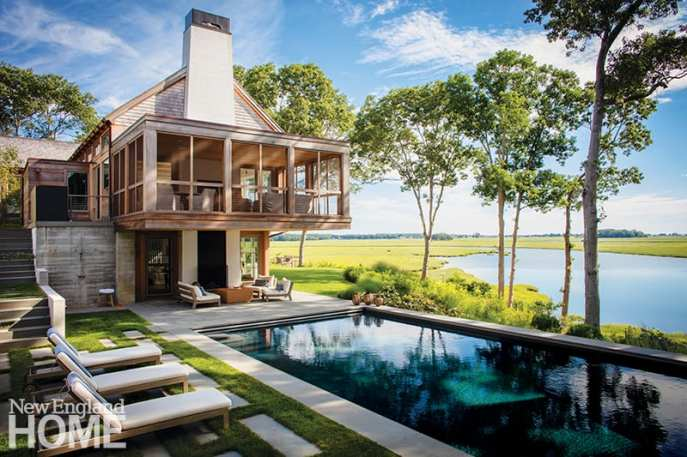 """This Duxbury, Massachusetts, house designed by Hutker Architects balances traditional expectations and modern possibilities on a steeply sloped site. Its black-capped """"Tory chimney"""" acknowledges local history while its cantilevered main level employs steel beams to create a sheltered pool deck on a limited footprint."""