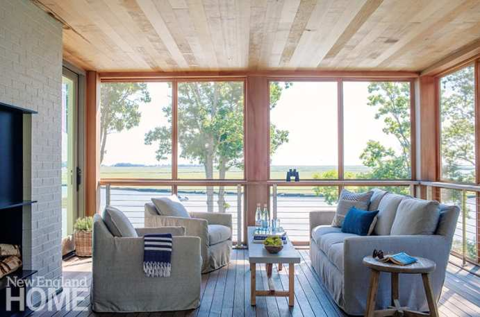 A pair of binoculars rests atop the railing on the porch, where bird-watching and napping compete with basking in the view and shoreline breezes; a bench serves as a narrow cocktail table between the comfy sofa and swivel chairs, both swathed in a linen-like outdoor fabric.