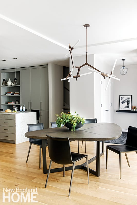 In the dining space, a linear Lindsey Adelman for Roll & Hill light fixture complements the sculptural shape of the dining table.