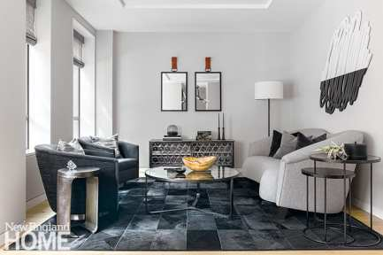 """""""If you're going with a monochromatic palette, how do you make it interesting?"""" asks designer Jessica Rogers. """"You do it with texture—materials that feel handcrafted."""" In the formal living room, that's evident in the leather-tabbed mirrors by Casamidy, the hair-on-hide Steven King carpet, and the laser-cut wood artwork by Nate Nettleton sourced from Boston Art."""