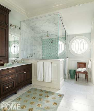 A window detail in the primary bathroom mimics the elliptical patterns found elsewhere in the home.