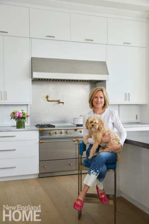 Connie Casey with the family's cockapoo, Charlotte; the wide-plank oak floors were sourced from Germany and inspired by the Casey's favorite NYC retreat, Crosby Street Hotel.