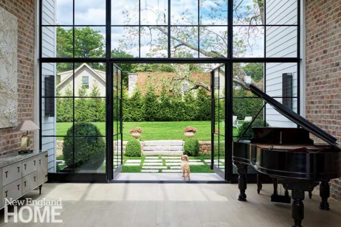 Visitors enter Connie and Mike Casey's Rowayton home via a steel-and-glass atrium, which also acts as an entertaining space. Antique brick from Belgium on the walls emphasizes the structure's industrial vibe. Outside, landscape designer Sidney Marshman planted arborvitae trees for privacy.