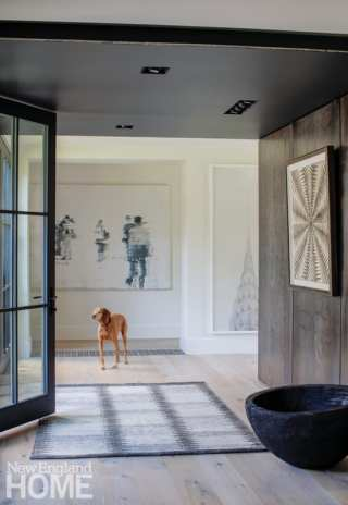 The home's front entry resides in a glass-walled connector topped with a light-filled study area for the clients' children on the level above.