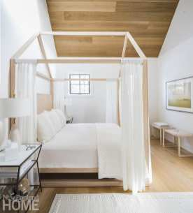 Canopy bed with white bedding.