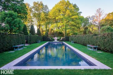 A long, lean reflecting/lap pool surrounded by Stick-designed benches stretches between the wisteria arbor and a fountain.