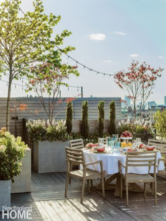 Boston roof top with a round table and contemporary chairs.