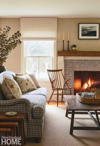 living room with a fireplace with a brick surround and reclaimed wood mantel.
