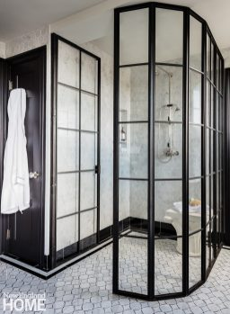 Primary bath with black and white palette and a metal shower door.