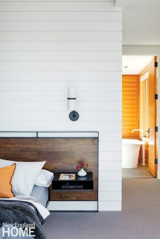 Main bedroom with shiplap wall and contemporary sconces.