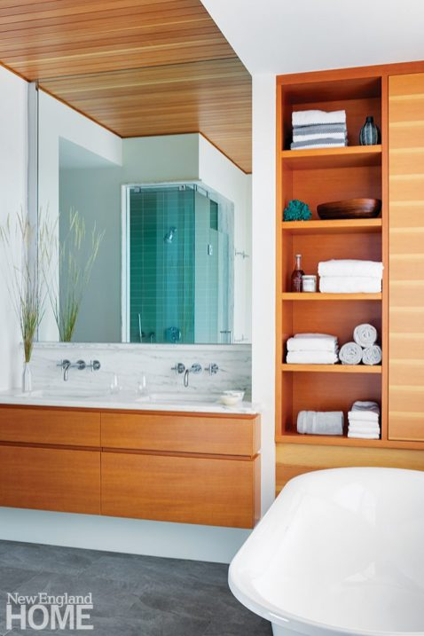 Contemporary bathroom with light wood, glass tiles, and a soaking tub.