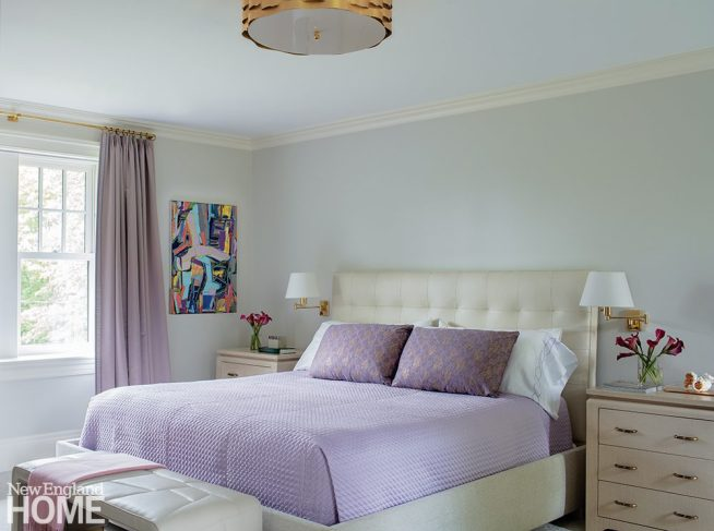 Primary bedroom with lavender drapes and bedding.