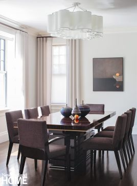 Dining room with white walls and a dark wooden table.