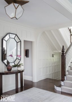 White entryway with demi-lune console.
